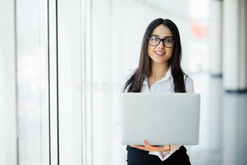 Νέα επιχειρησιακή γυναίκα που εργάζεται στο πολυτελές γραφείο της που κρατά ένα lap-top στεμένος ενάντια στο πανοραμικό παράθυρο  στοκ εικόνες