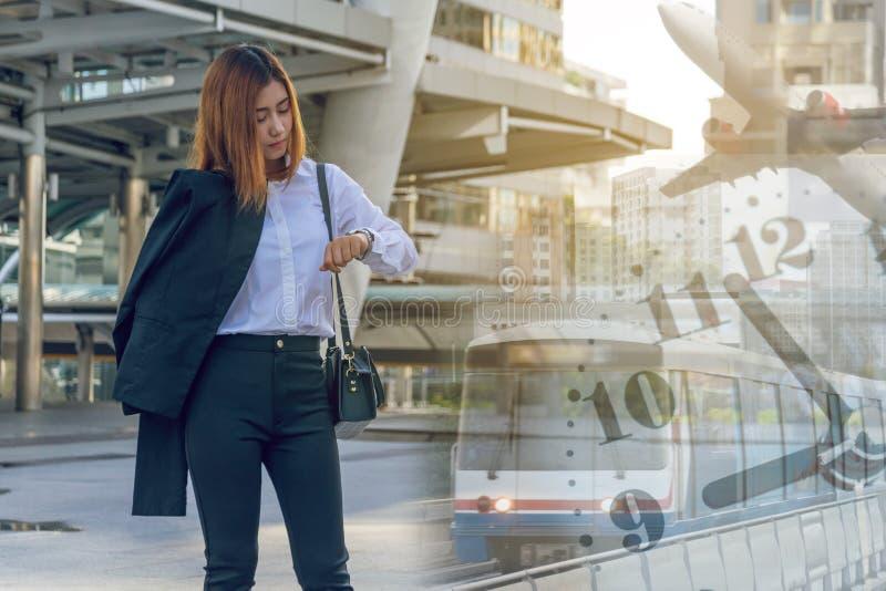 Νέα επιχειρησιακή γυναίκα που ελέγχει το χρόνο στο ρολόι της στοκ εικόνα με δικαίωμα ελεύθερης χρήσης