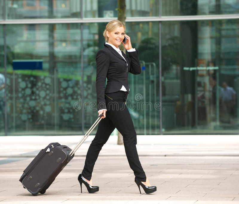 Νέα επιχειρησιακή γυναίκα που περπατά και που μιλά στο τηλέφωνο στην πόλη στοκ φωτογραφίες με δικαίωμα ελεύθερης χρήσης