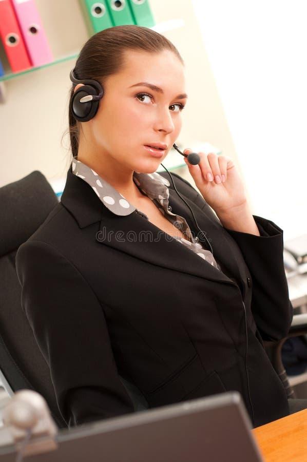 Νέα επιχειρησιακή γυναίκα που φορά τα ακουστικά στοκ εικόνα