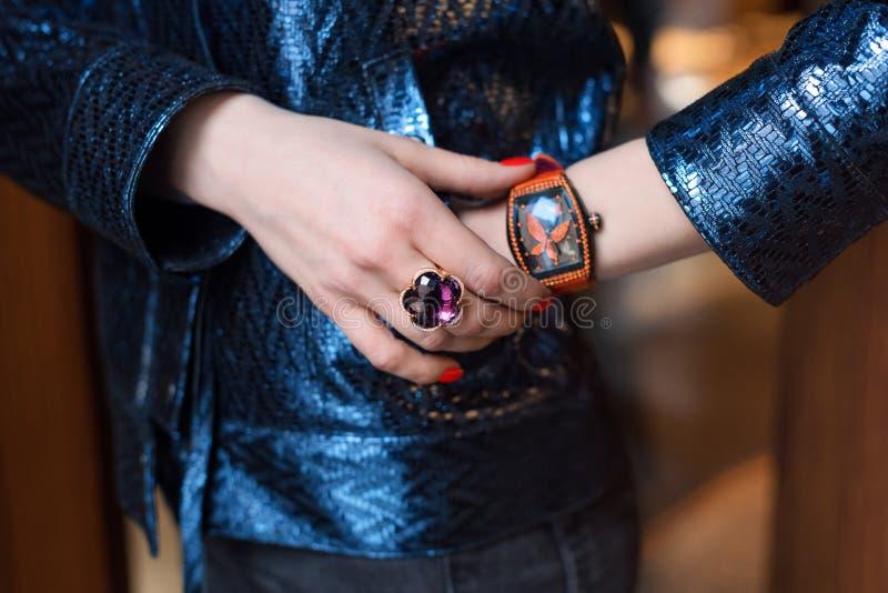 Νέα επιχειρησιακή γυναίκα που φορά το ρολόι πολυτέλειας και το πολύτιμο κόσμημα Μοντέρνα γυναικεία εξαρτήματα στοκ φωτογραφία