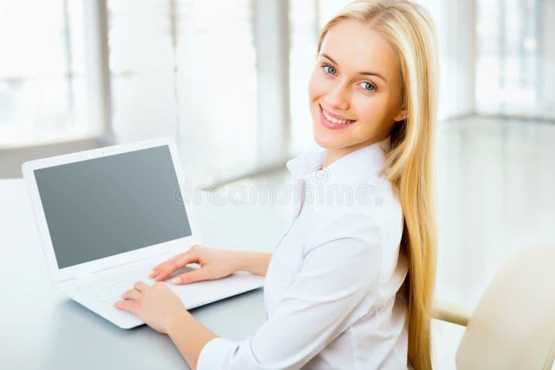 Νέα επιχειρησιακή γυναίκα που χρησιμοποιεί το lap-top στοκ εικόνα