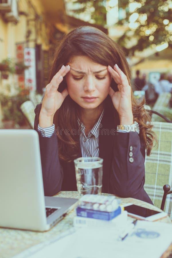 Νέα επιχειρησιακή γυναίκα στον καφέ που λειτουργεί με τον επικεφαλής πόνο στοκ φωτογραφία με δικαίωμα ελεύθερης χρήσης