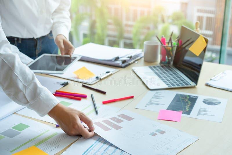 Νέα επιχειρησιακή ομαδική εργασία που λειτουργεί με το έγγραφο επιχειρησιακών εκθέσεων στο γραφείο στοκ εικόνα
