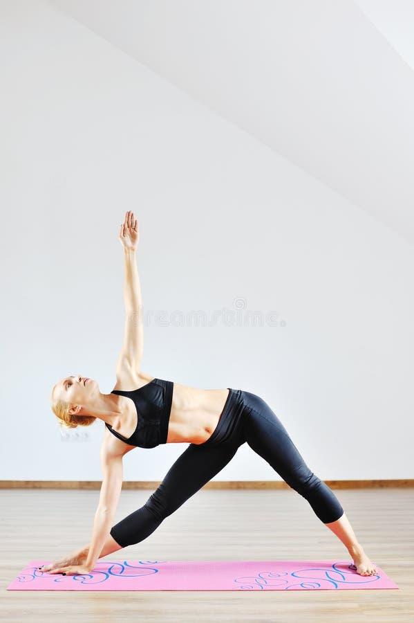Νέα λεπτή αθλήτρια που τεντώνει στο εσωτερικό στοκ εικόνα