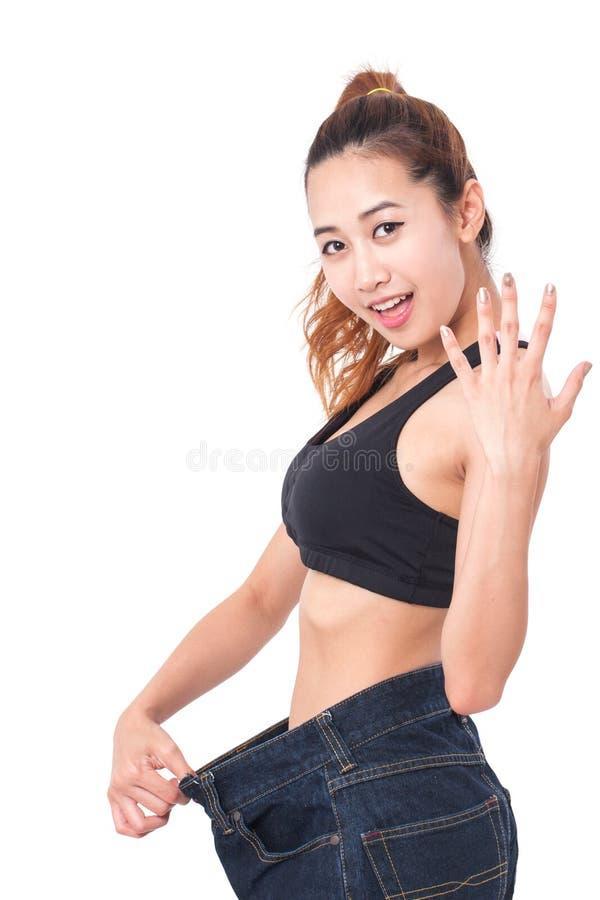 Νέα λεπτή γυναίκα που φορά τα πάρα πολύ μεγάλα τζιν με την υπόδειξη του δάχτυλου στοκ εικόνες