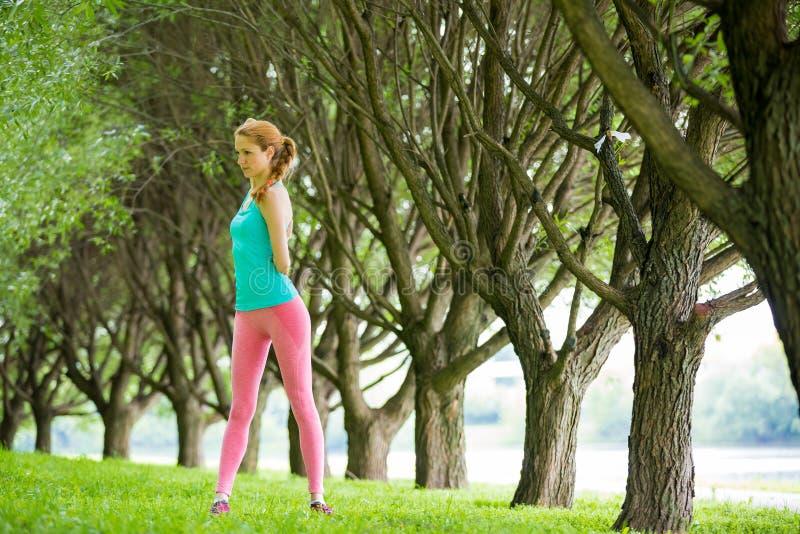 Νέα λεπτή γυναικεία κατάρτιση στο πάρκο στοκ εικόνα