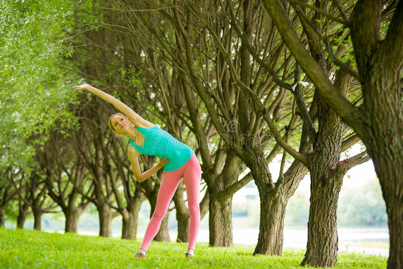 Νέα λεπτή γυναικεία κατάρτιση στο πάρκο στοκ φωτογραφία