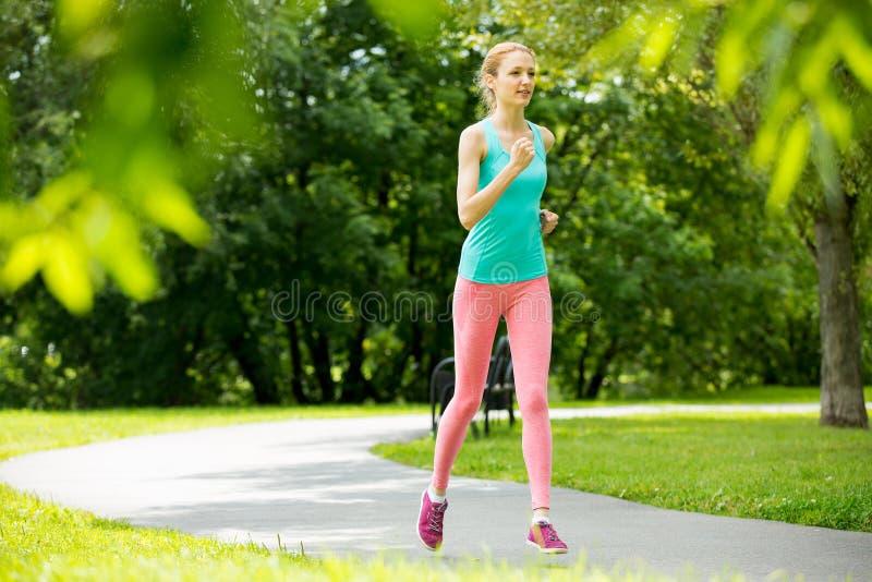 Νέα λεπτή κυρία που τρέχει στο πάρκο στοκ εικόνες με δικαίωμα ελεύθερης χρήσης