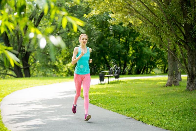 Νέα λεπτή κυρία που τρέχει στο πάρκο στοκ εικόνα με δικαίωμα ελεύθερης χρήσης