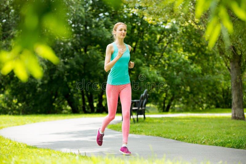 Νέα λεπτή κυρία που τρέχει στο πάρκο στοκ εικόνα