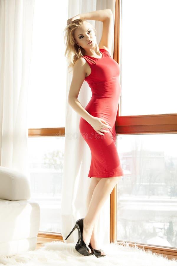 Νέα λεπτή προκλητική γυναίκα στο κόκκινο φόρεμα στοκ εικόνες