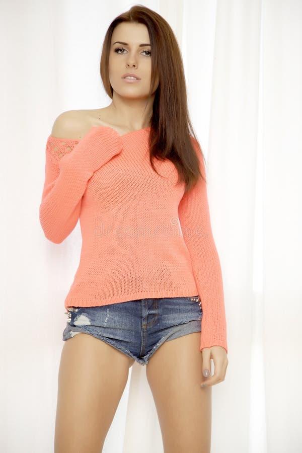 Νέα λεπτή προκλητική γυναίκα στο πορτοκαλί πουλόβερ ενάντια στο παράθυρο στοκ εικόνες