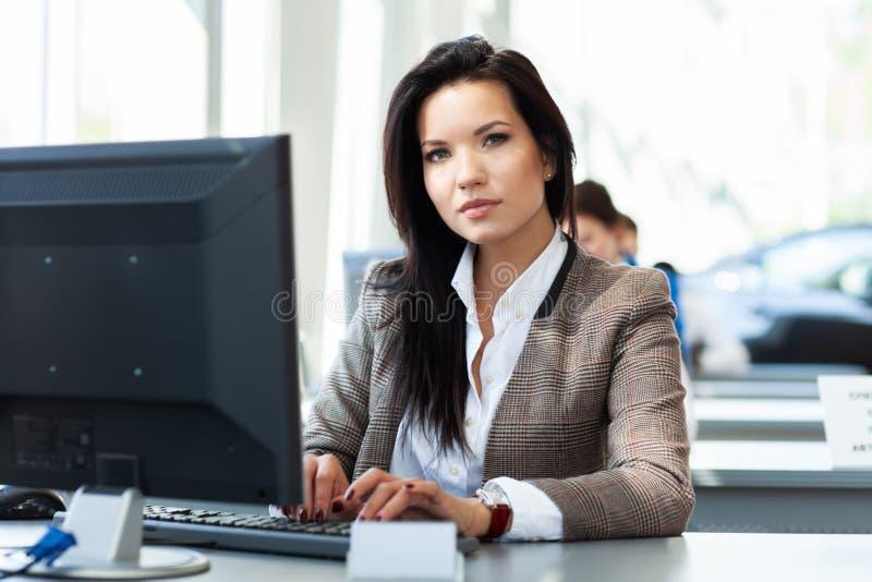Νέα εργασία γυναικών στην αρχή, καθμένος στο γραφείο, που χρησιμοποιεί το lap-top στοκ εικόνες
