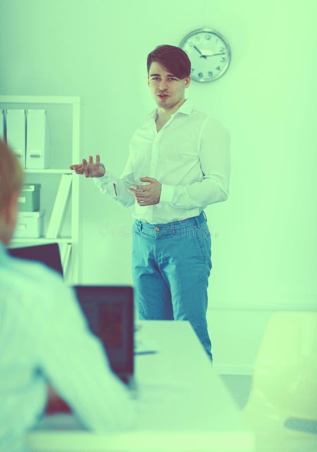 Νέα εργασία επιχειρηματιών στην αρχή, καθμένος στο γραφείο στοκ εικόνες
