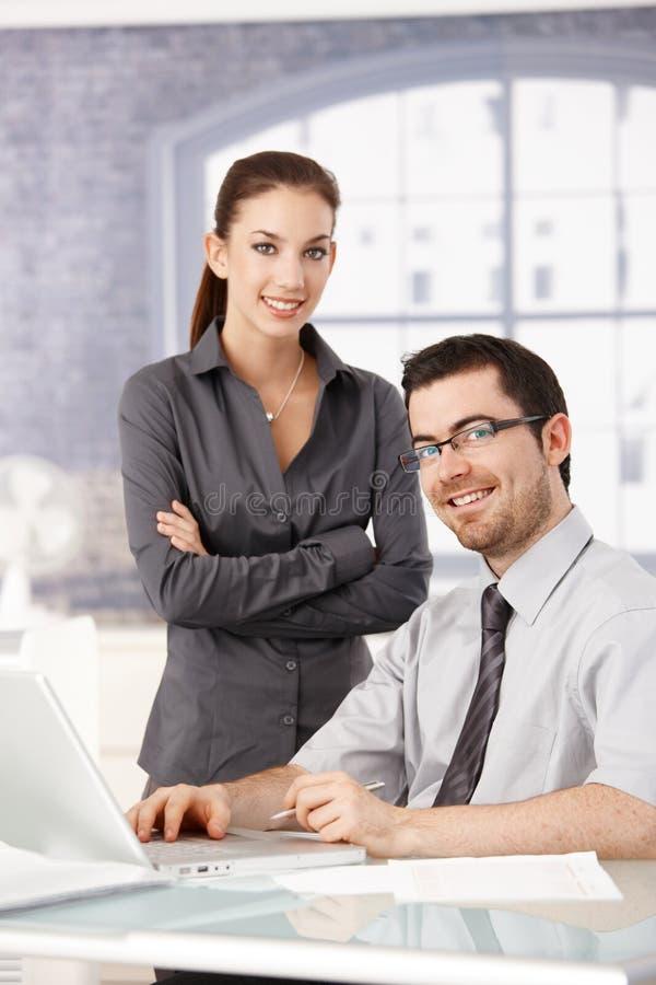 Νέα εργασία συναδέλφων που χαμογελά στο φωτεινό γραφείο στοκ φωτογραφίες με δικαίωμα ελεύθερης χρήσης