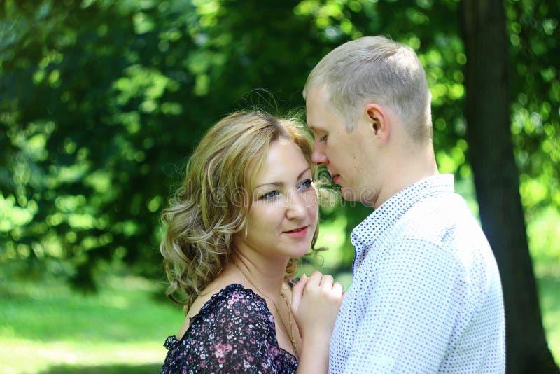 Νέα ερωτευμένη χαλάρωση ζευγών υπαίθρια ιστορία αγάπης φιλήματος κοριτσιών κήπων αγοριών στοκ εικόνα