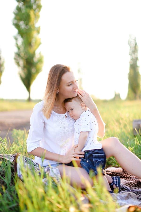 Νέα ευρωπαϊκή συνεδρίαση μητέρων με λίγο παιδί στο καρό, χλόη στο υπόβαθρο στοκ εικόνες