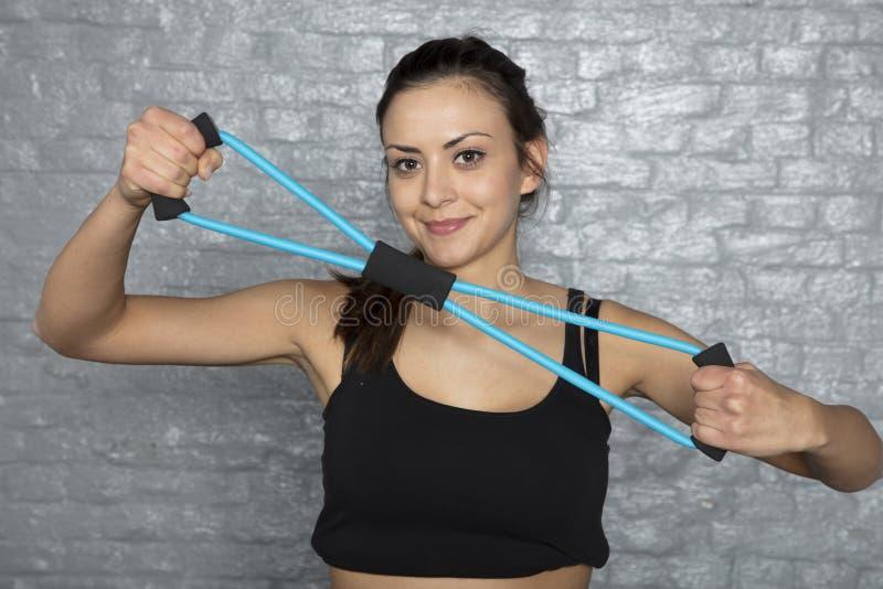 Νέα ευτυχής αθλητική γυναίκα που κάνει τις ασκήσεις στοκ εικόνες