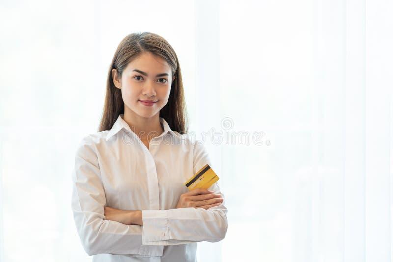 Νέα ευτυχής ασιατική πιστωτική κάρτα εκμετάλλευσης γυναικών για on-line να ψωνίσει στο σπίτι στοκ φωτογραφία με δικαίωμα ελεύθερης χρήσης