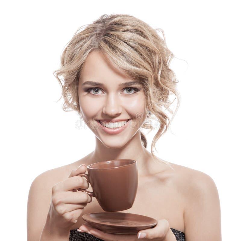 Νέα ευτυχής γυναίκα με έναν αρωματικό καφέ στα χέρια. Απομονωμένος στοκ εικόνες με δικαίωμα ελεύθερης χρήσης