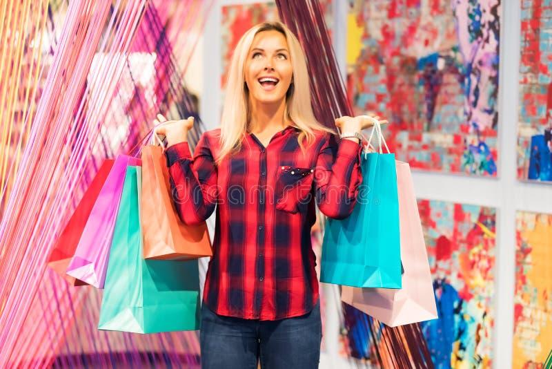 Νέα ευτυχής γυναίκα με πολλές τσάντες αγορών στο sto μόδας στοκ φωτογραφίες με δικαίωμα ελεύθερης χρήσης