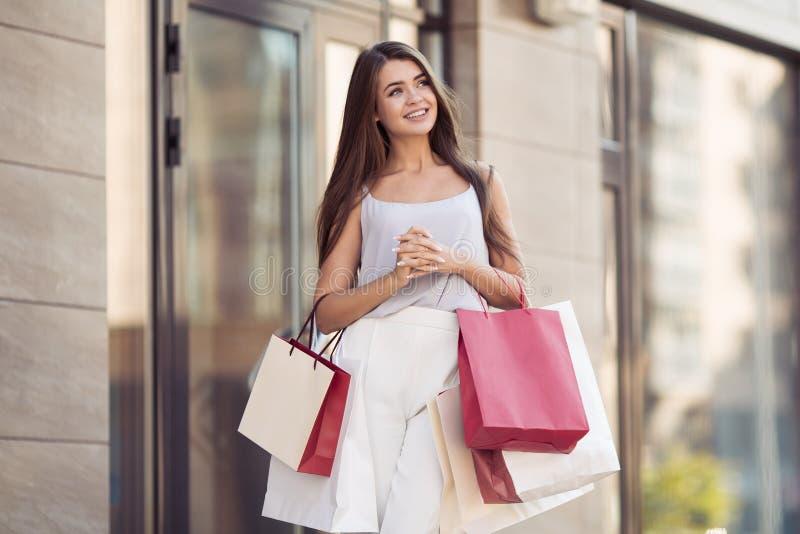Νέα ευτυχής γυναίκα με τις τσάντες αγορών που περπατά στην οδό στοκ φωτογραφία με δικαίωμα ελεύθερης χρήσης