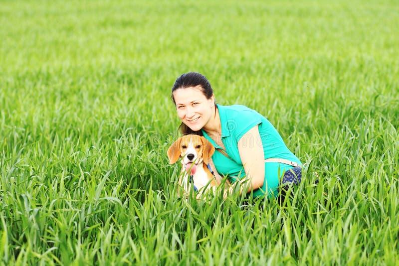 Νέα ευτυχής γυναίκα με το σκυλί λαγωνικών στοκ φωτογραφίες