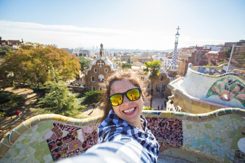 Νέα ευτυχής γυναίκα που κάνει selfie το πορτρέτο με το smartphone στο πάρκο Guell, Βαρκελώνη, Ισπανία Όμορφο κορίτσι που εξετάζει στοκ φωτογραφία με δικαίωμα ελεύθερης χρήσης