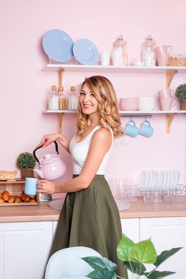 Νέα ευτυχής γυναίκα που κατασκευάζει τον καφέ ή το τσάι στο σπίτι στην κουζίνα Ξανθό όμορφο κορίτσι που έχει το πρόγευμά της πρίν στοκ εικόνες