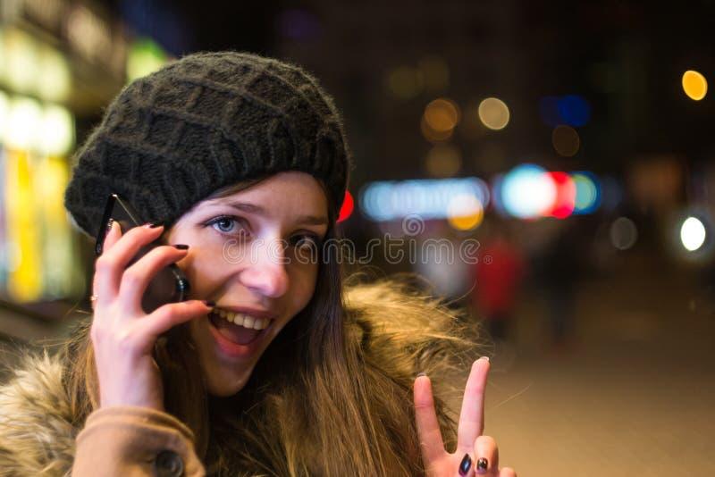Νέα ευτυχής γυναίκα που μιλά στο κινητό τηλέφωνο τη νύχτα το χειμώνα στοκ φωτογραφίες με δικαίωμα ελεύθερης χρήσης
