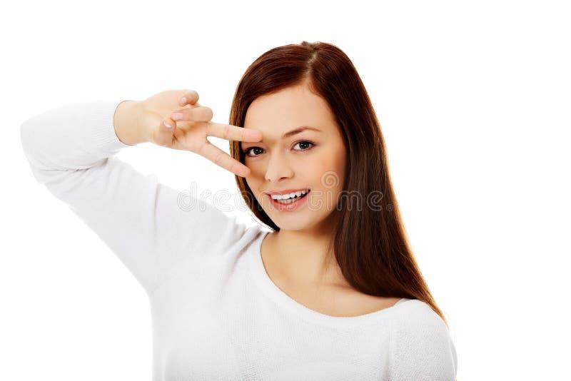 Νέα ευτυχής γυναίκα που παρουσιάζει δύο δάχτυλα στοκ φωτογραφία