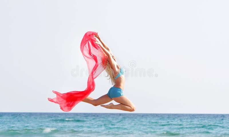Νέα ευτυχής γυναίκα που πηδά με το κόκκινο μαντίλι στοκ φωτογραφία με δικαίωμα ελεύθερης χρήσης
