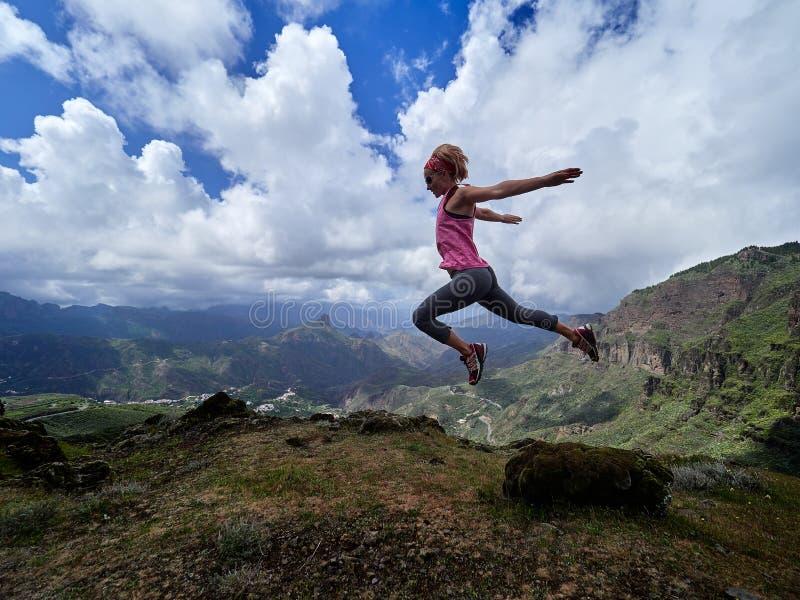 Νέα ευτυχής γυναίκα που πηδά πάνω από το βουνό στοκ φωτογραφία με δικαίωμα ελεύθερης χρήσης
