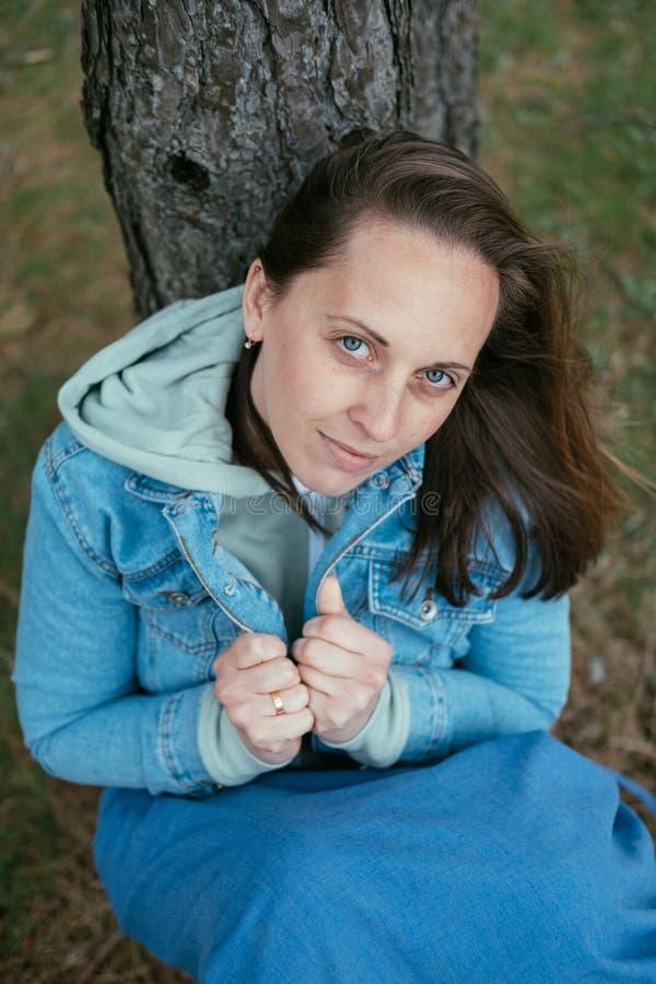 Νέα ευτυχής γυναίκα που χαμογελά σε ένα πουλόβερ το φθινόπωρο, που κάθεται έξω στοκ φωτογραφία με δικαίωμα ελεύθερης χρήσης