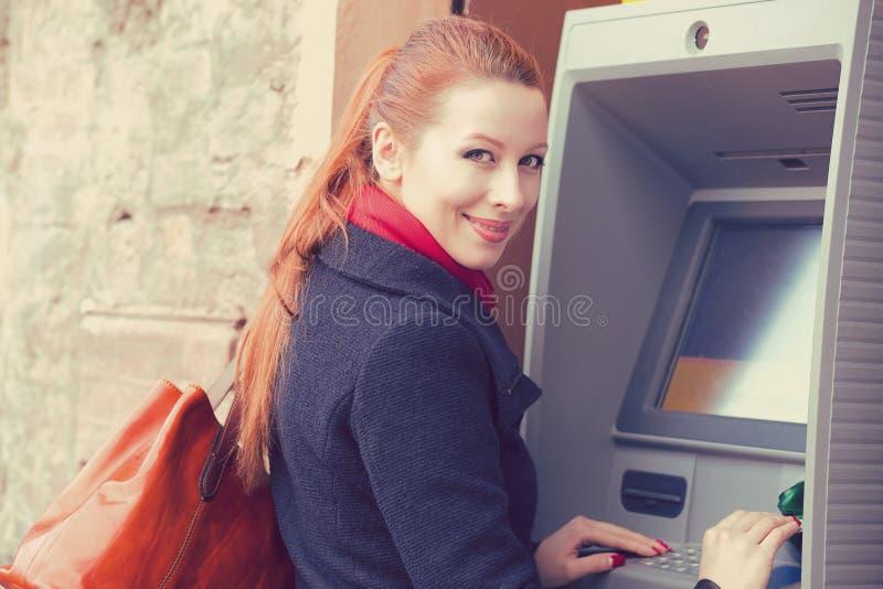 Νέα ευτυχής γυναίκα που χρησιμοποιεί το ATM στοκ φωτογραφίες με δικαίωμα ελεύθερης χρήσης