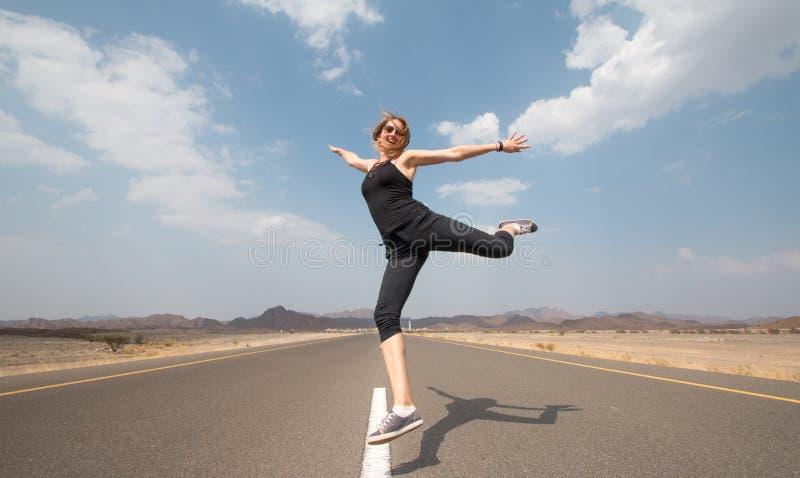 Νέα ευτυχής γυναίκα σε έναν κενό δρόμο στην έρημο του Ομάν στοκ φωτογραφία με δικαίωμα ελεύθερης χρήσης