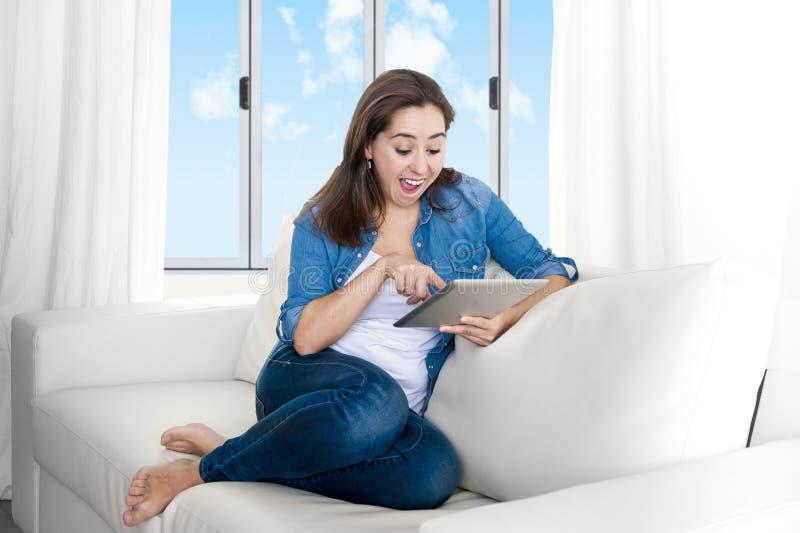 Νέα ευτυχής γυναίκα στον καναπέ που απολαμβάνει στο σπίτι χρησιμοποιώντας την ψηφιακή ταμπλέτα στοκ εικόνες