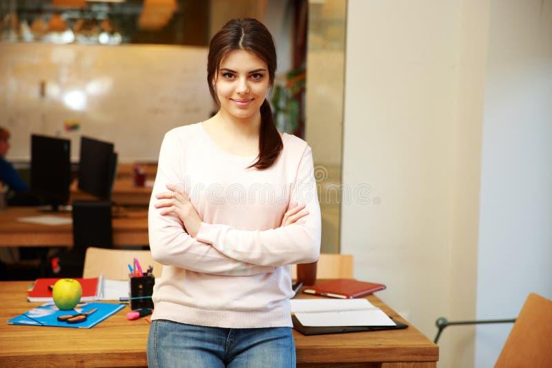 Νέα ευτυχής γυναίκα στο γραφείο στοκ φωτογραφία