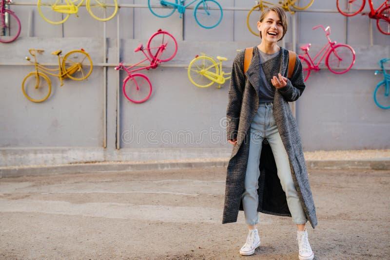 Νέα ευτυχής ελκυστική με κοντά μαλλιά γυναίκα brunette μπροστά από τον τοίχο ποδηλάτων στοκ φωτογραφία με δικαίωμα ελεύθερης χρήσης