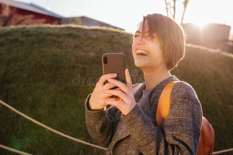 Νέα ευτυχής ελκυστική με κοντά μαλλιά γυναίκα brunette με το τηλέφωνο σε ένα πάρκο στοκ φωτογραφίες