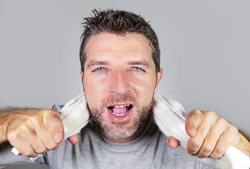 Νέα ευτυχής και ελκυστική πετσέτα εκμετάλλευσης ατόμων στο λαιμό του που εξετάζει τον καθρέφτη λουτρών που χαμογελά το εύθυμο και στοκ φωτογραφία