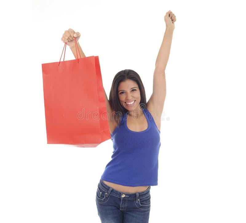 Νέα ευτυχής και όμορφη ισπανική γυναίκα που κρατά το κόκκινο χαμόγελο τσαντών αγορών συγκινημένο απομονωμένος στο λευκό στοκ εικόνα με δικαίωμα ελεύθερης χρήσης