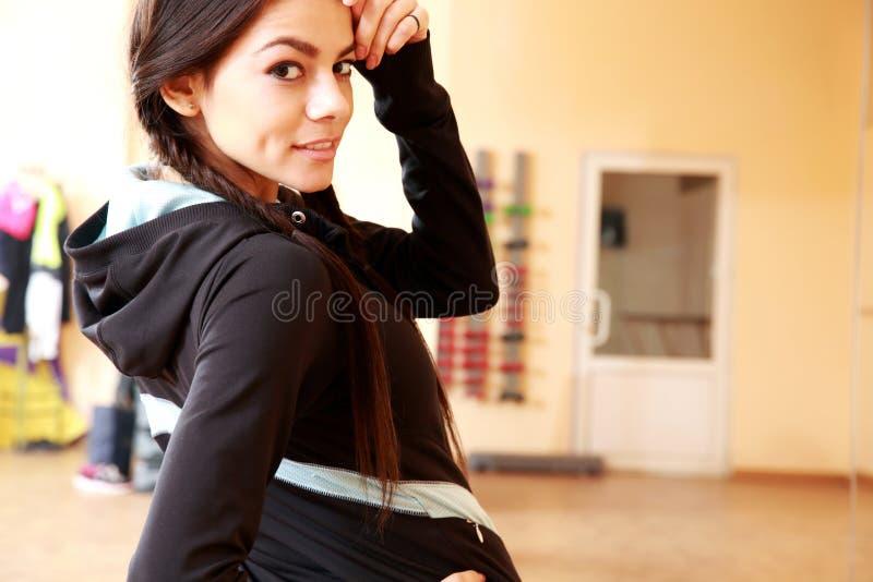 Νέα ευτυχής κατάλληλη γυναίκα που εξετάζει τη κάμερα στοκ εικόνα