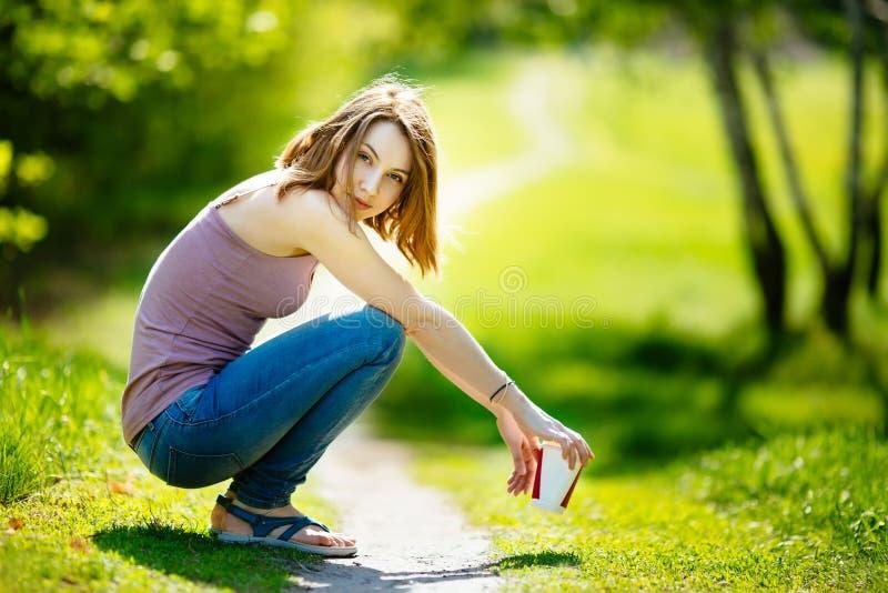 Νέα ευτυχής καυκάσια ξανθή γυναίκα με τη συνεδρίαση ποτών καφέ στο πάρκο στοκ εικόνες