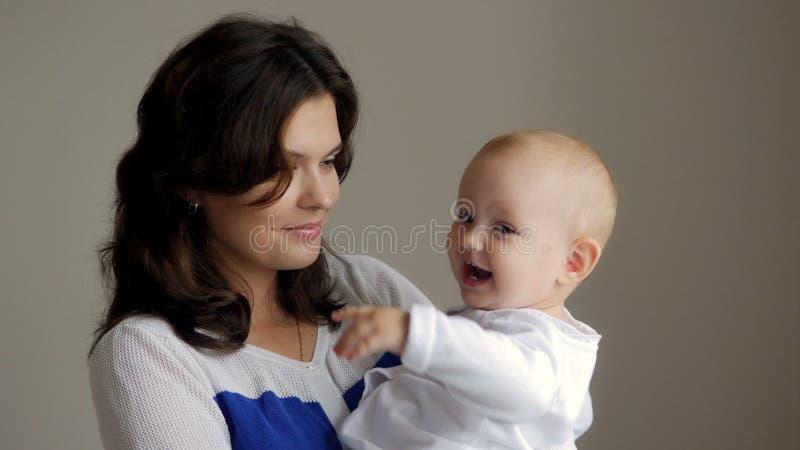Νέα ευτυχής μητέρα που κρατά το νεογέννητο παιδί της διάνυσμα εικόνας οικογενειακών κατοικιών jpg Όμορφο χαμόγελο Mom και μωρό απ στοκ εικόνα με δικαίωμα ελεύθερης χρήσης