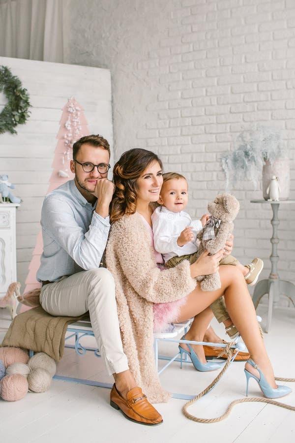 Νέα ευτυχής οικογένεια με το μωρό στο στούντιο ντεκόρ Χριστουγέννων στοκ εικόνες