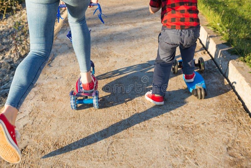 Νέα ευτυχής οικογένεια με των παιδιών που έχουν τη διασκέδαση στη φύση Το αγόρι με τη μητέρα του οδηγά ένα μηχανικό δίκυκλο στοκ εικόνες