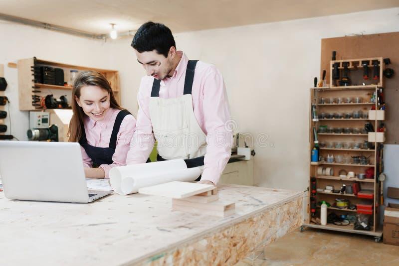 Νέα ευτυχής οικογένεια που στέκεται σε έναν πάγκο εργασίας σε ένα εργαστήριο ξυλουργικής, που γράφει ένα πρόγραμμα Οικογενειακή ε στοκ εικόνα με δικαίωμα ελεύθερης χρήσης