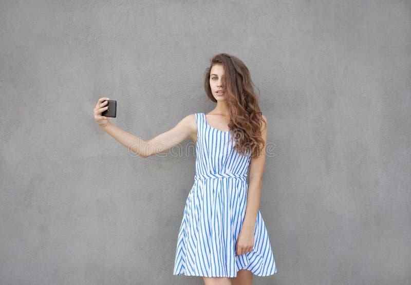 Νέα ευτυχής χαμογελώντας όμορφη γυναίκα στο ελαφρύ φόρεμα με τη μακροχρόνια τοποθέτηση τρίχας brunette σγουρή ενάντια στον τοίχο  στοκ εικόνες